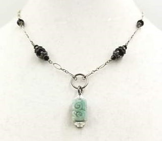 Jadeite pendant on a sterling silver and onyx necklace.