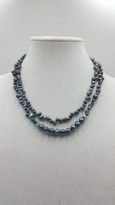 Multi-tone peacock pearl necklace on navy silk. 41
