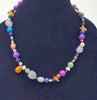 Multi-stone cosmic necklace with sterling silver clasp on white silk.
