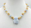 "Precious yellow jadeite, & blue lace agate on pale pink silk with vintage sterling silver clasp. 18"" Length."