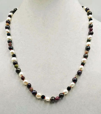 Beautiful pearl & tourmaline necklace, hand-knotted with crimson silk. A 14KWG clasp finishes the look of simple elegance. 24