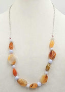 "Sterling silver, bi-tone agate necklace on rose silk. 28"" Length."