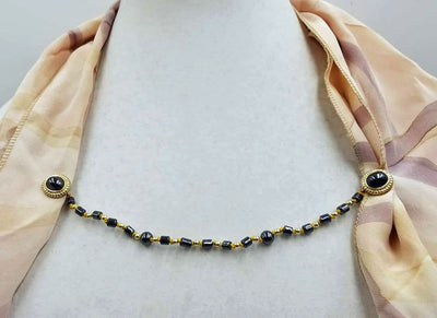 Gold-tone, hematite & gold-filled cape clasp on golden silk.