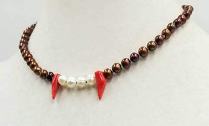 "Fangs, beautiful fangs. Sterling Silver, chocolate pearls, white pearls, & red coral, fang necklace. Hand-knotted on taupe silk.  17"" length."