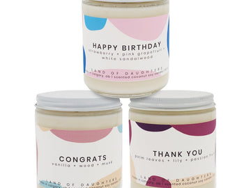 Three soy candles in glass jars with white lids. The candles have white labels across them with different colored abstract shapes. They are sitting in a beige basket on a white background.