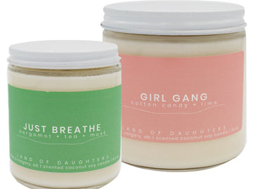 A collection of scented candles on a white fluffy background. The candles each have a different colored label that indicates a scent name, they also each have a white metal lid. There are eleven candles lined up in three rows.