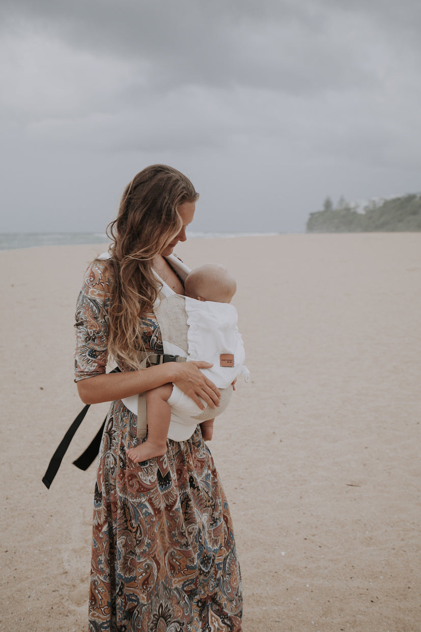 Mother carrying baby in Zarpar Bebe linen baby carrier at the beach