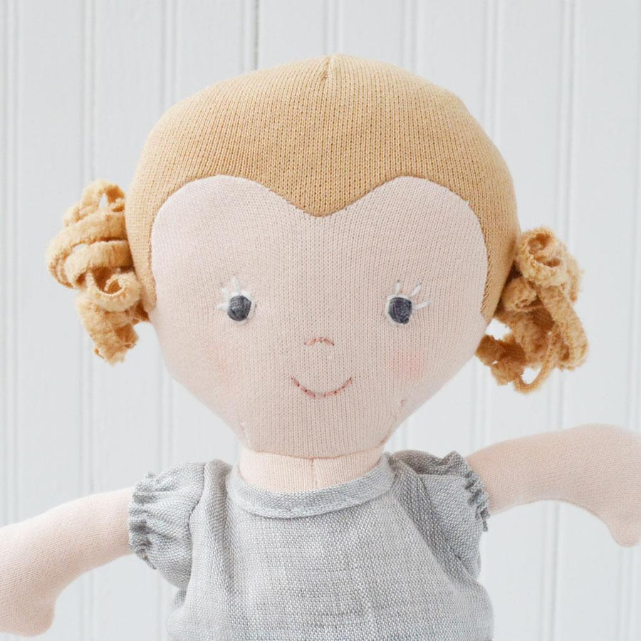 Hazel Village organic cotton Fern doll. She has blonde hair and is dressed in grey linen dress