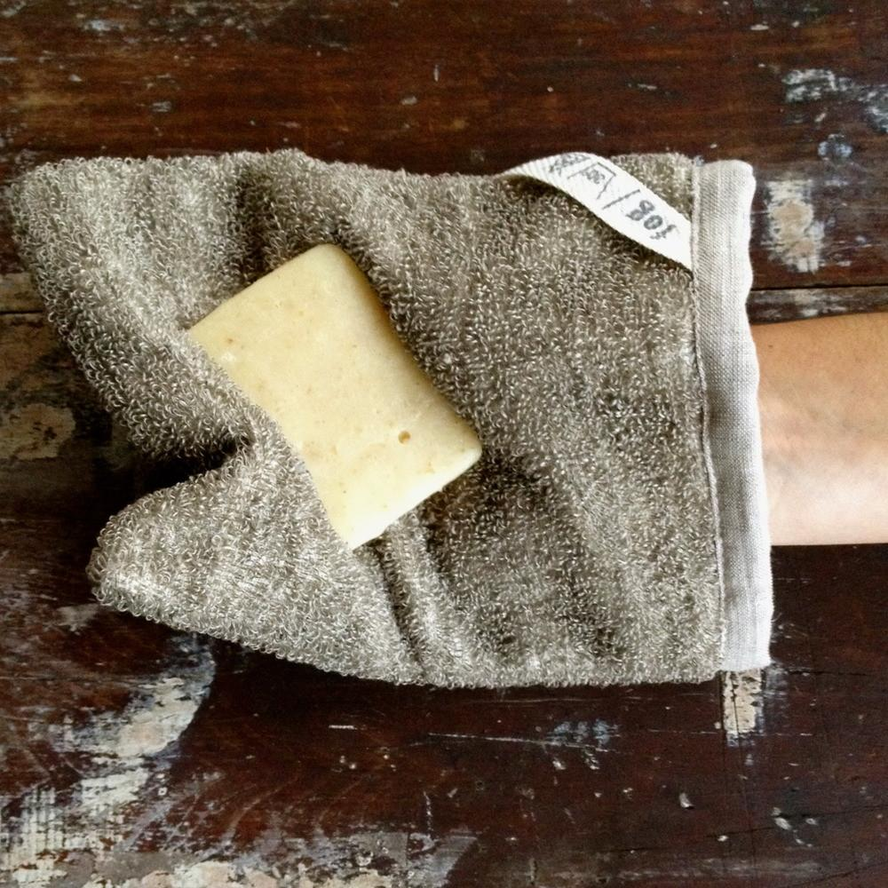 Fog Linen Work massage bath mitten in natural linen on a person's hand holding a bar of soap