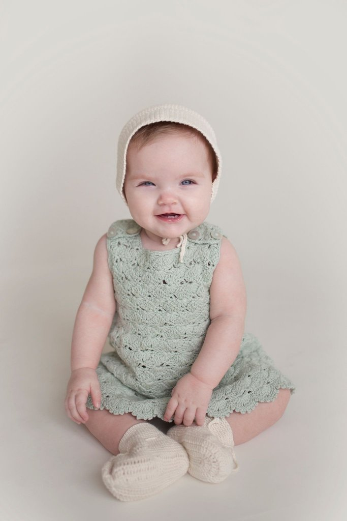 Baby wearing Miou organic cotton Bisou Dress in seafoam green with bonnet and booties