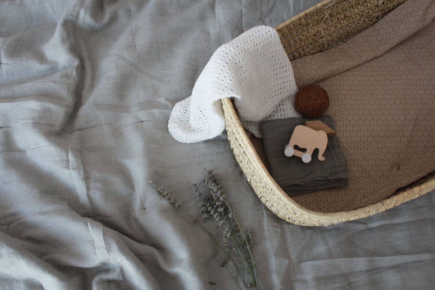 Pinch Toys Mini Elephant wooden toy in a baby basket with grey and white bedding