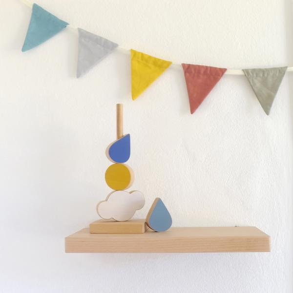 The Wandering Workshop Catch the Cloud Stacking Toy on a wooden shelf with colourful bunting in background