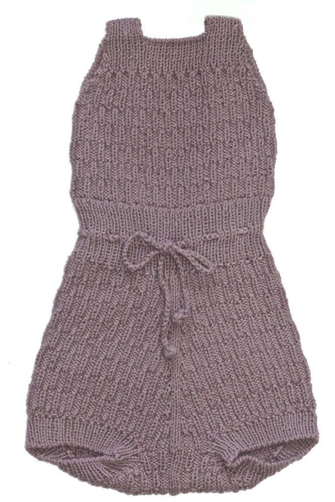 Baby wearing Miou organic cotton Caterpillar romper in plum with cream bonnet