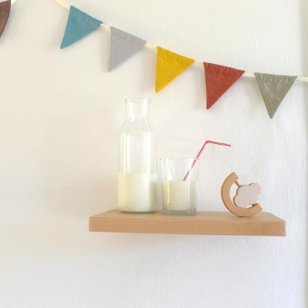 The Wandering Workshop cloud teether rattle on a wooden shelf next to a bottle and a glass of milk and a colourful bunting behind it