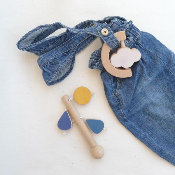 The Wandering Workshop cloud teether rattle flatlay with denim overalls