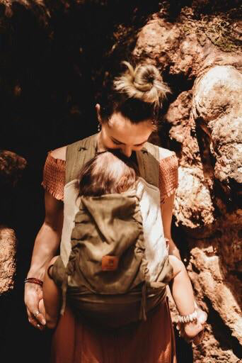 Mother carrying baby in a Zarpar Bebe linen wrap baby carrier in earth brown