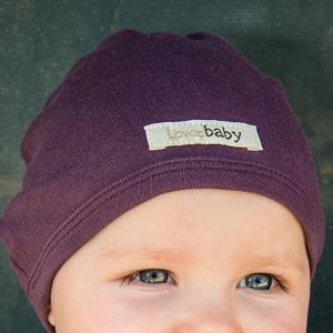 Baby wearing Loved Baby organic cotton cute cap in eggplant