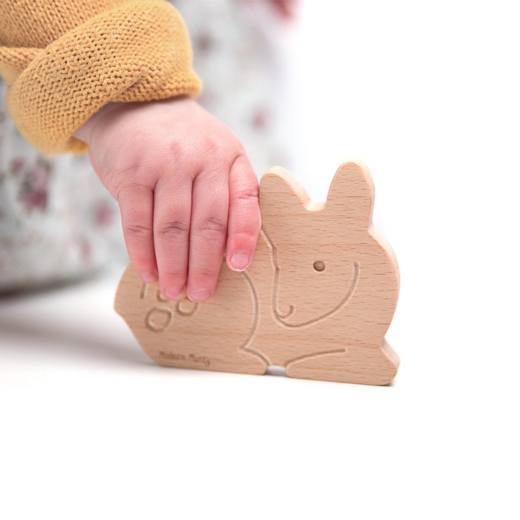 Toddler's hand holding a Modern Month wooden fawn teether