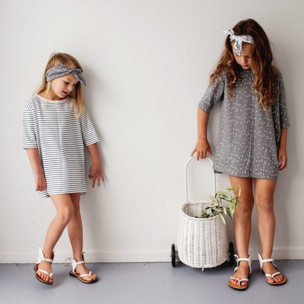 Two girls wearing Le Edit organic cotton oversized stripe dresses