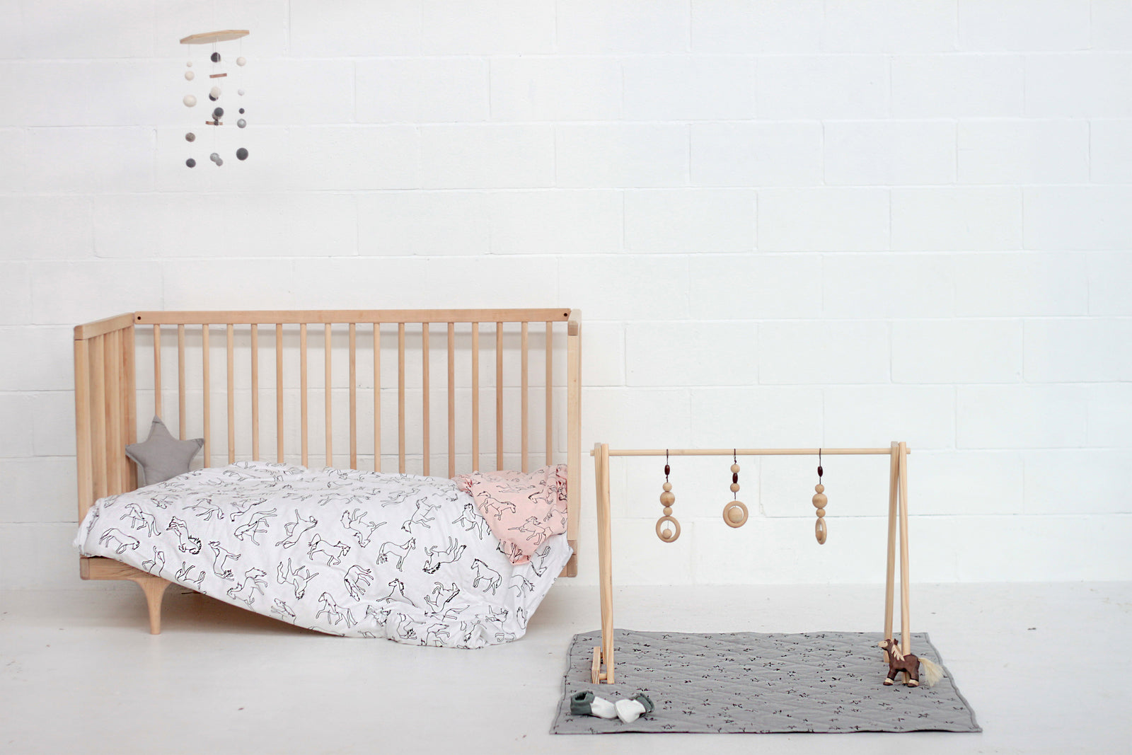Burrow and Be Dreaming of Horses and Stars printed bedding on a cot with a wooden play gym next to it