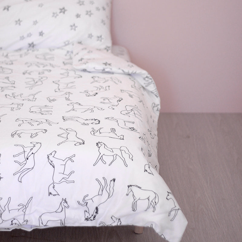 Burrow and Be Dreaming of Horses and Stars printed bedding on a bed