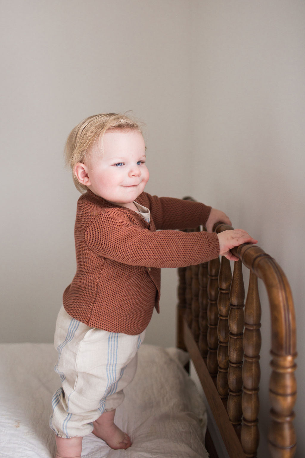 Baby wearing Fin and Vince Wrap Cardigan Spice