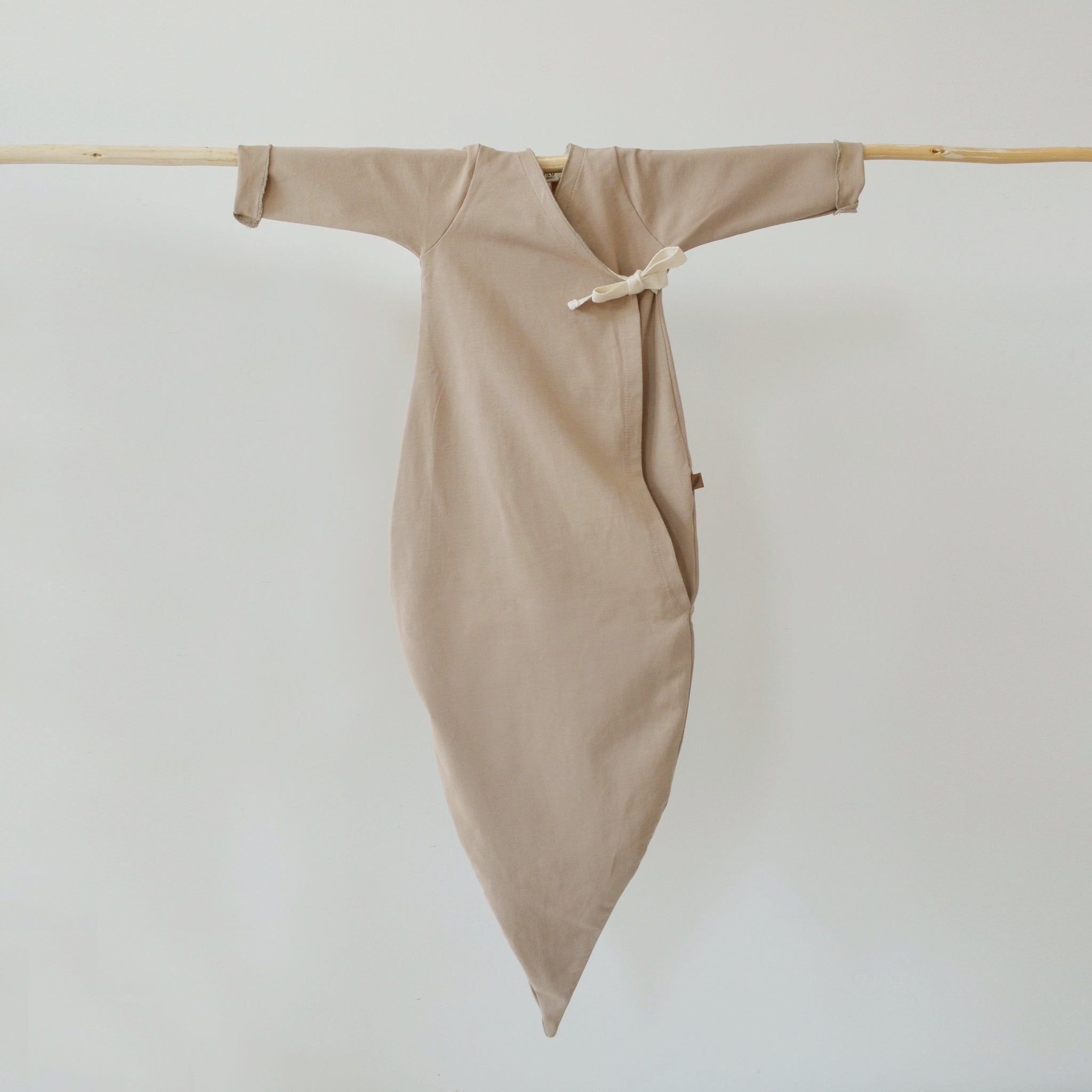 KidWild Organics organic cotton baby kimono gown in dune (neutral beige) hanging on wooden rod