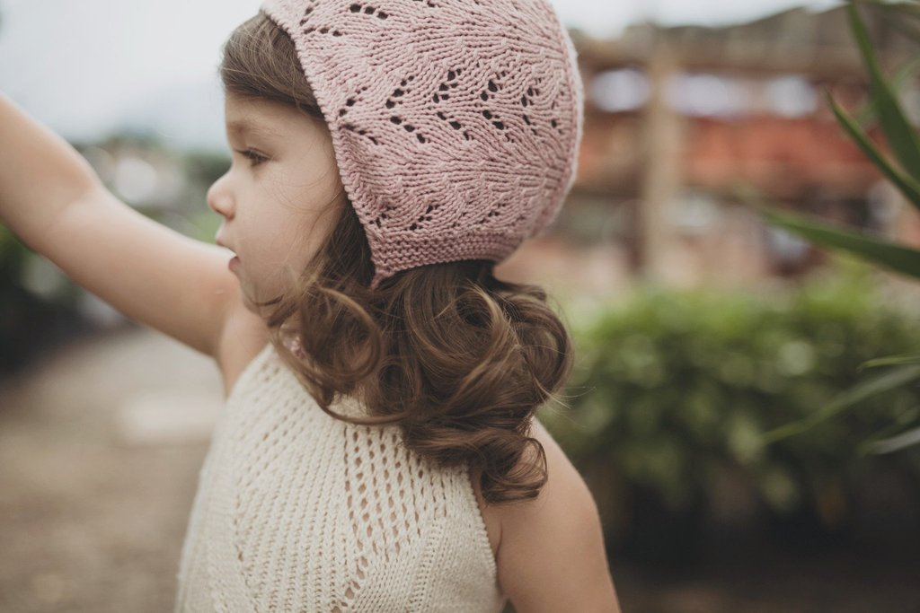 Girl wearing Miou organic cotton Lacy bonnet in pink