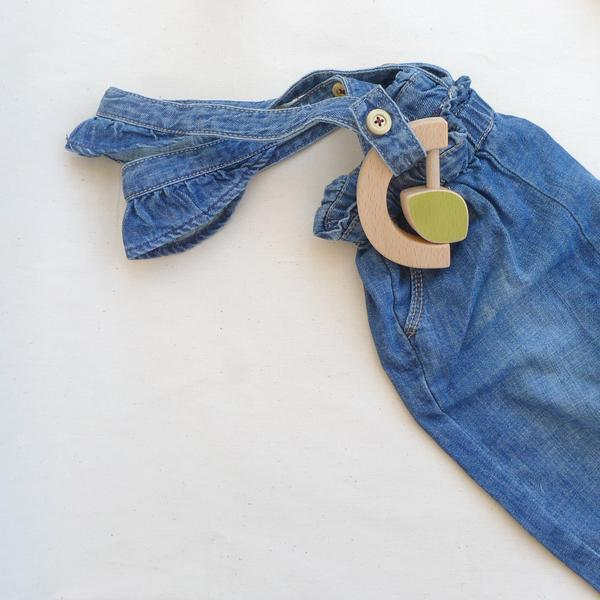 Flatlay of The Wandering Workshop wooden leaf teething rattle sitting on top of denim overalls
