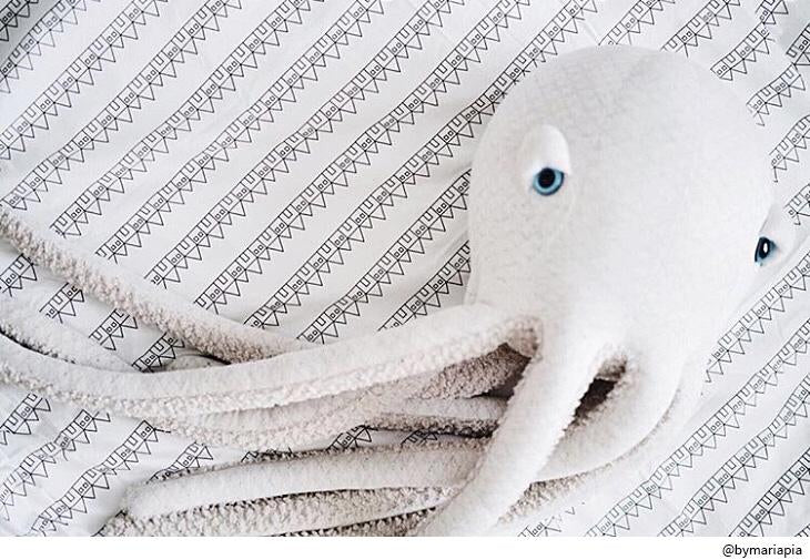 Stuffed octopus toy sitting on on a bed dressed with Swedish Linens organic cotton sheet in the Lindbacken print in black and white