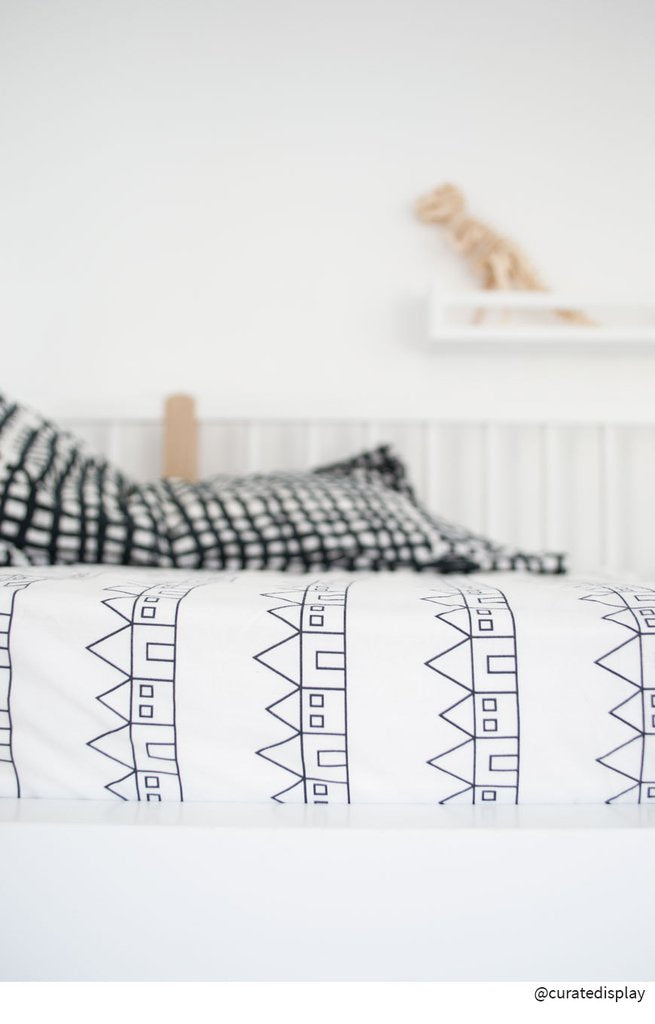 Side view of a bed dressed with Swedish Linens organic cotton sheet in the Lindbacken print in black and white