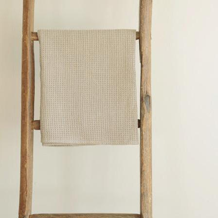Fog Linen Work waffle towel in natural linen hanging on a wooden ladder