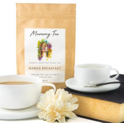 Packet of organic loose leaf Mummy Tea Mama's Breakfast with two porcelain tea cups, book and flower