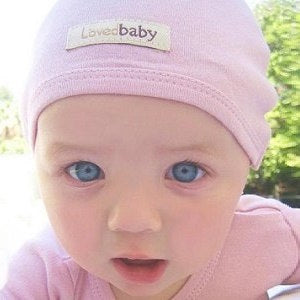 Baby wearing Loved Baby organic cotton cute cap in mauve