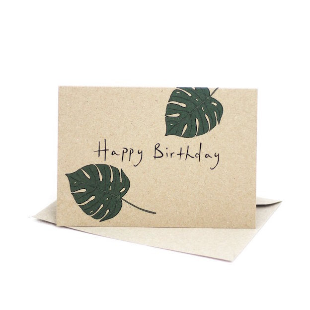 Deer Daisy kraft board greeting card that features an illustration of two monstera leaves and says Happy Birthday