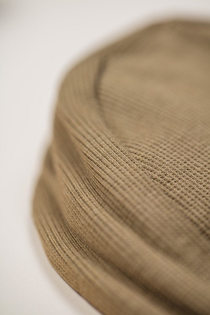 Close up of Little Indi organic cotton baby bonnet in moss green