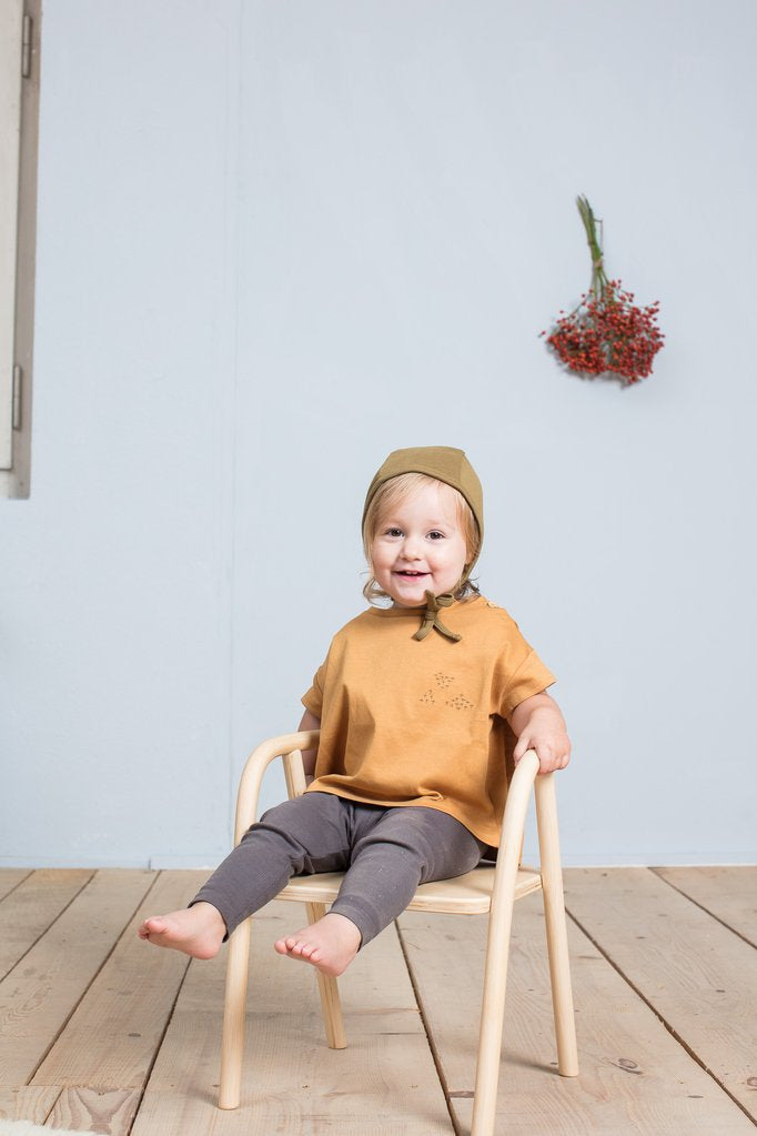 Toddler wearing Little Indi organic cotton baby bonnet in moss green