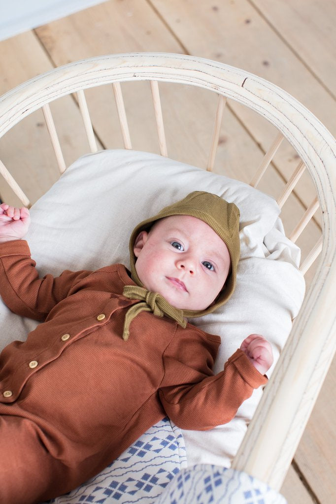 Toddler wearing Little Indi organic cotton ribbed jumpsuit in rust and bonnet in moss green