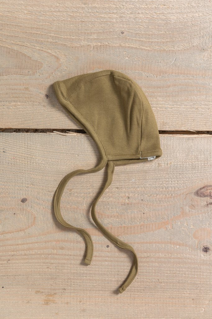 Little Indi organic cotton baby bonnet in moss green on wooden background