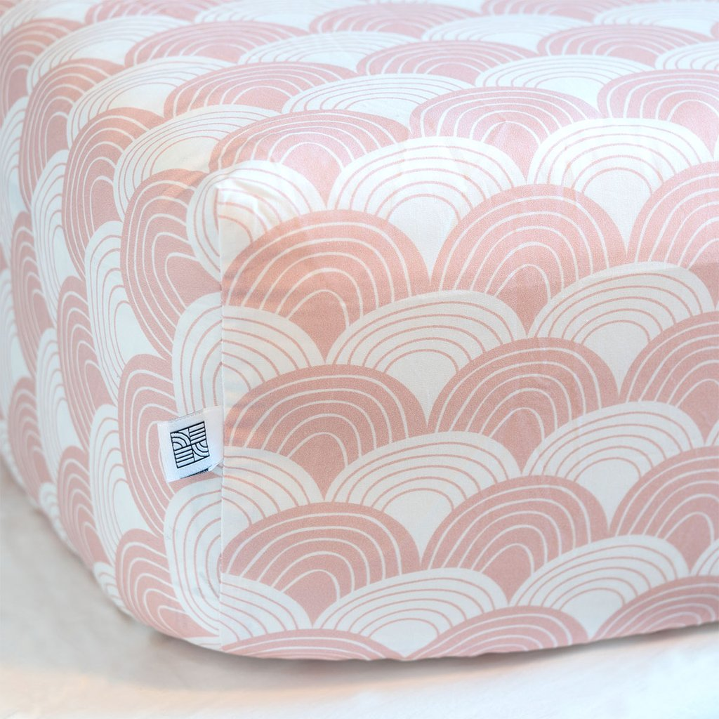 Swedish Linens Nudy Pink Rainbows organic cotton fitted sheet on a mattress