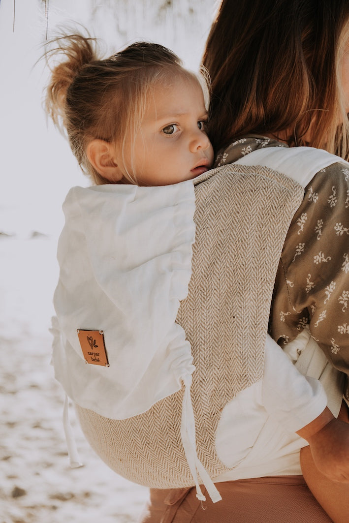 Close up of toddler being carried on her mother's back in Zarpar Bebe linen baby carrier