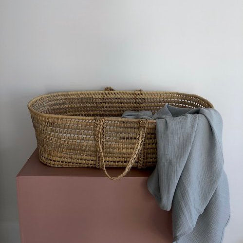 Thursday's Child organic cotton gauze wrap in haze - a light grey colour - draped on the side of a baby moses basket