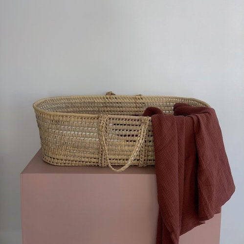 Thursday's Child organic cotton gauze wrap in rust draped on the side of a baby moses basket