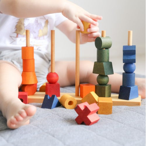 Close up of baby playing with Wooden Story Rainbow Stacking Toy