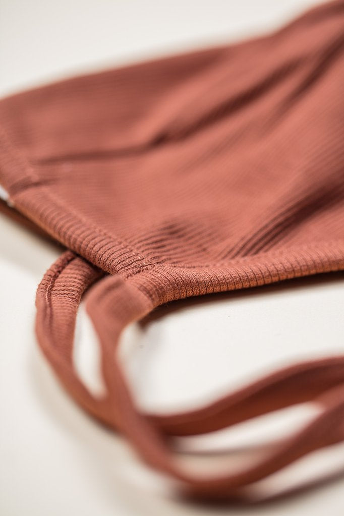 Close up of Little Indi organic cotton ribbed baby bonnet in rust