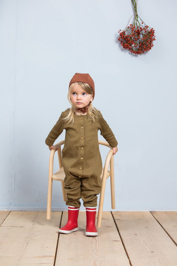 Toddler wearing Little Indi organic cotton ribbed jumpsuit in moss and bonnet in rust