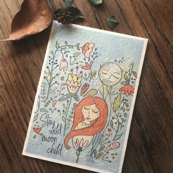Mama and Daisy plantable greeting card - Stay Wild Moon Child - on top of a wooden table
