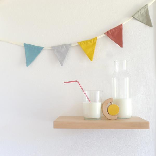 The Wandering Workshop wooden sun rattle teether on a shelf with glass and jug of milk