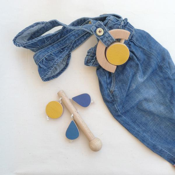 Flatlay of The Wandering Workshop wooden sun rattle teether on denim overalls