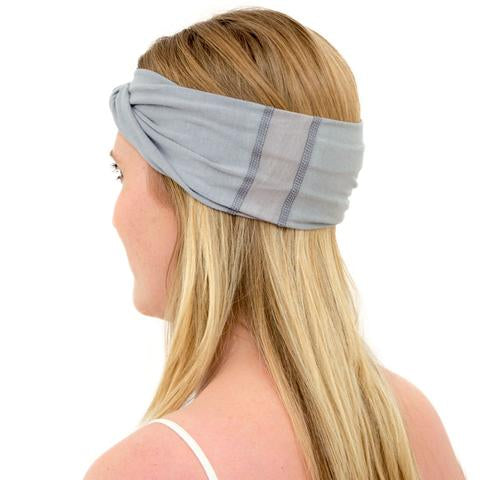 Back of Model wearing Kooshoo organic cotton yoga twist headband in limestone grey